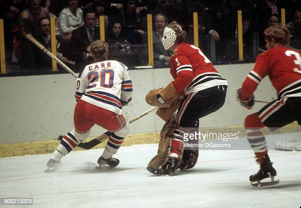 Gene Carr of the New York Rangers trys to skates around goalie Gary Smith of the Chicago Blackhawks as Keith Magnuson of the Blackhawks looks on...
