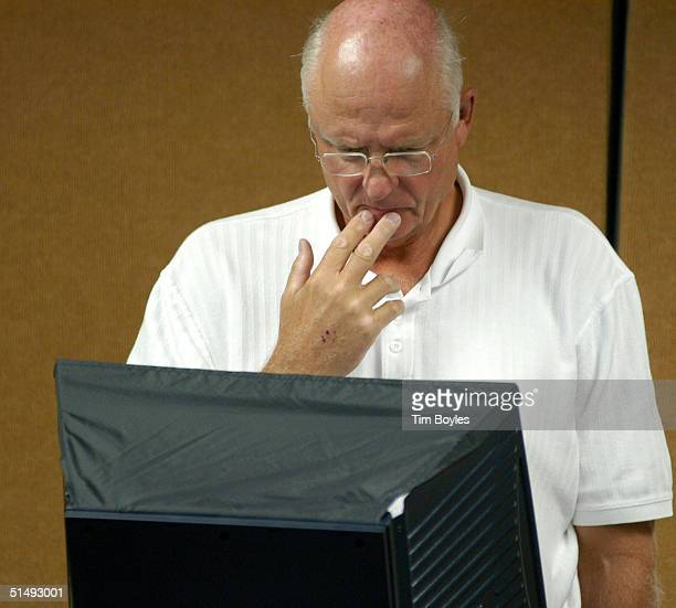 Gene England ponders his vote while using an electronic machine to cast his ballot on the first day of early voting in the presidential election at...