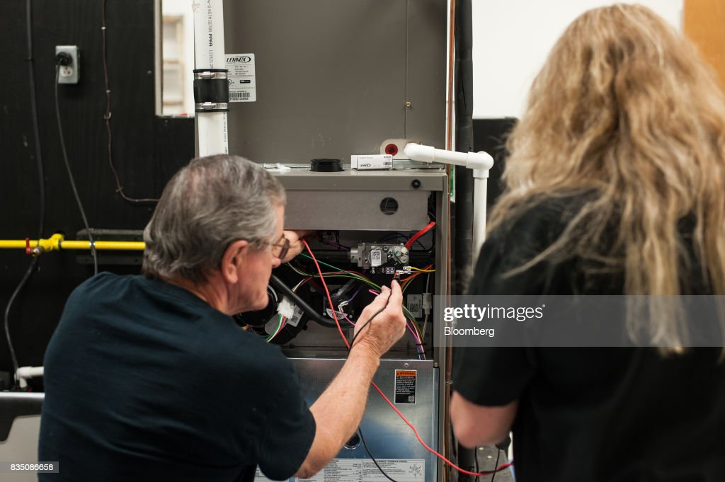 Gene Everly, left, of Greensboro, Pennsylvania, demonstrates how to test a furnace in a training classroom at the Penn Commercial Business/Technical School in Washington, Pennsylvania, U.S., on Tuesday, Aug. 15, 2017. Everly built long wall mining equipment for 20 years before industry declines led to massive layoffs. While fracking has created a bonanza of jobs, displaced coal miners and their communities are sometimes left out of the boom. Thats because many of the jobs require highly technical skills and are often going to experienced workers brought in from out of state who then move on to the next job without sinking roots. Photographer: Stephanie Strasburg/Bloomberg via Getty Images