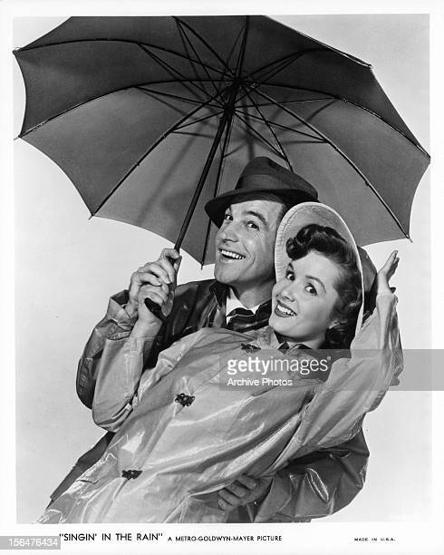 Gene Kelly and Debbie Reynolds stand under an umbrella in publicity portrait for the film 'Singin' In The Rain' 1952