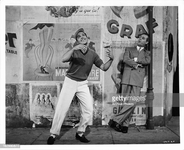 Gene Kelly dances in the street next to Georges Guétary in a scene from the film 'An American In Paris' 1951