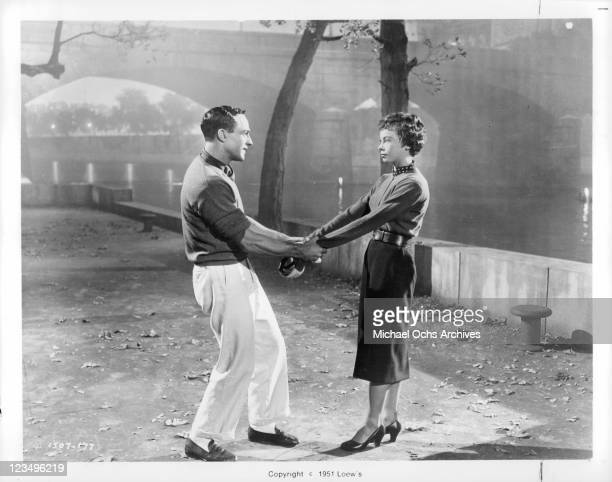 Gene Kelly holding Leslie Caron's arms in a scene from the film 'An American In Paris' 1951
