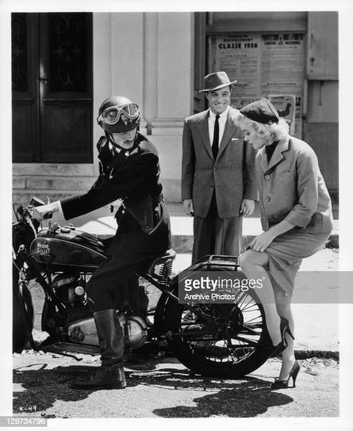 Gene Kelly smiles as Barbara Laage shows leg to French policeman in a scene from the film 'Happy Road' 1957