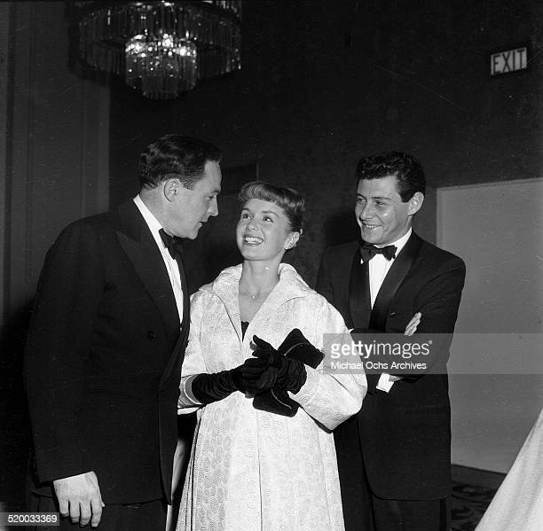 Gene Kelly talks with Debbie Reynolds and Eddie Fisher as they attend the Screen Producers Awards in Los AngelesCA