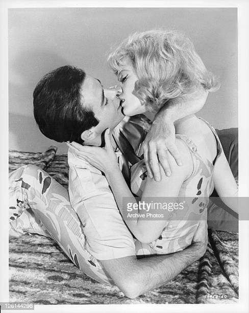 Gene Kirkwood and Mimsy Farmer passionately kissing in a scene from the film 'Hot Rods To Hell' 1966