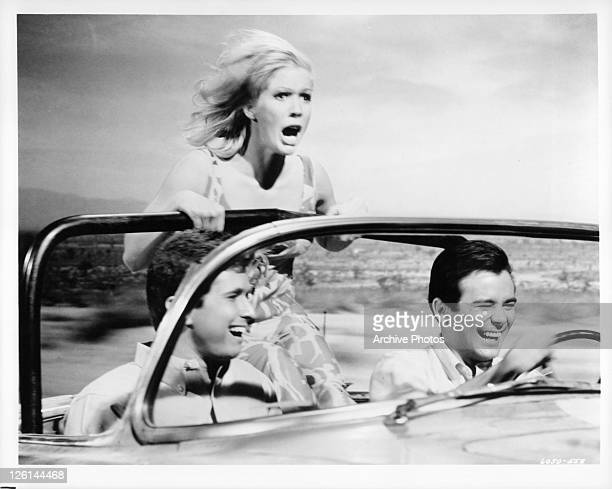 Gene Kirkwood driving a convertiable as Mimsy Farmer stands in the back seat with wind in her hair in a scene from the film 'Hot Rods To Hell' 1966