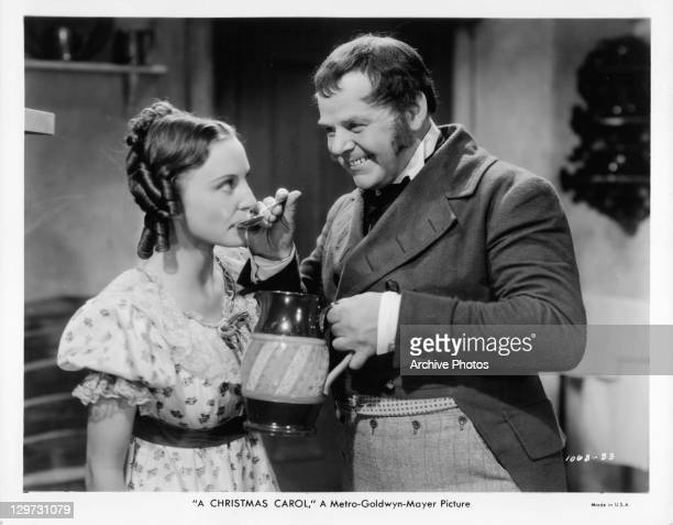 Gene Lockhart providing spoonful to unidentified woman in a scene from the film 'A Christmas Carol' 1938