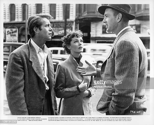 Gene Nelson and Phyllis Kirk looking up at Sterling Hayden in a scene from the film 'Crime Wave' 1954