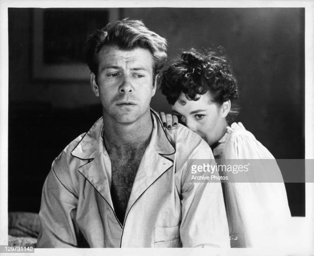 Gene Nelson on the bed with Phyllis Kirk leaning against him in a scene from the film 'Crime Wave' 1954