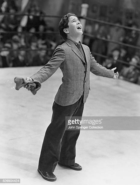 Gene Reynolds as the young Tommy McCoy singing in a boxing ring in the 1938 film The Crowd Roars