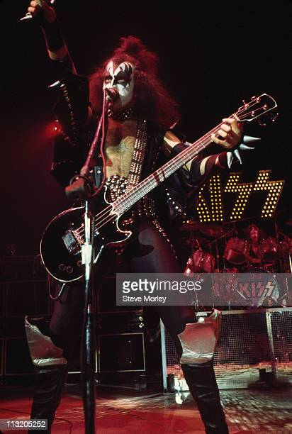 Gene Simmons, U.S. Rock bassist and singer with rock band Kiss, playing the bass guitar and singing into a mirophone during a live concert...