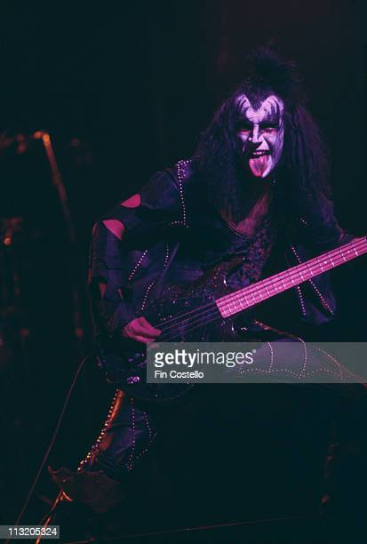 Gene Simmons US rock bassist and singer with rock band Kiss playing the bass guitar and adopting his trademark stance with his tongue sticking out...