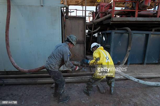 Gene Starbuck left and Julio Perez right both floor hands work at connecting tubes on the Raven Oil Drilling rig near Watford City ND Oct 1 2013 In...