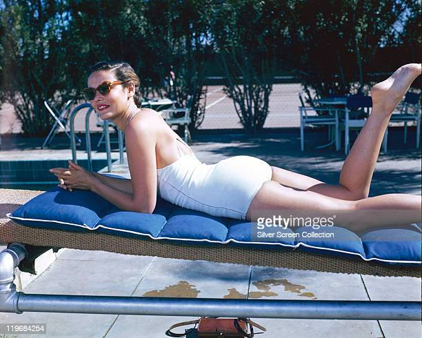 Gene Tierney US actress laying on her front sunbathing on a sunlounger wearing a white swimsuit and sunglasses circa 1940