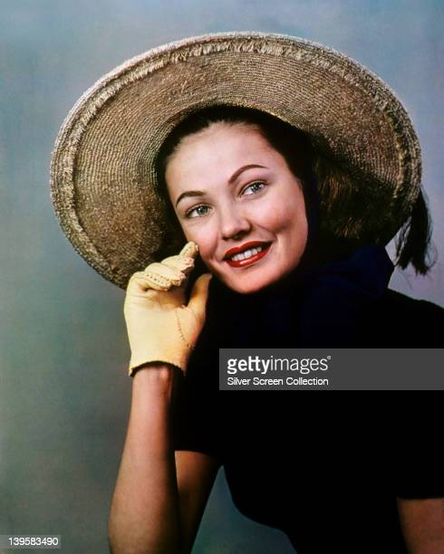 Gene Tierney US actress wearing a black top with yellow gloves and a widebrimmed straw hat in a studio portrait circa 1945
