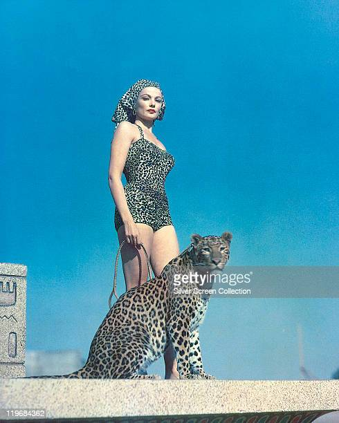 Gene Tierney US actress wearing a leopard print swimsuit and headscarf posing alongside a leopard which Tierney holds on a lead 27th July 1954