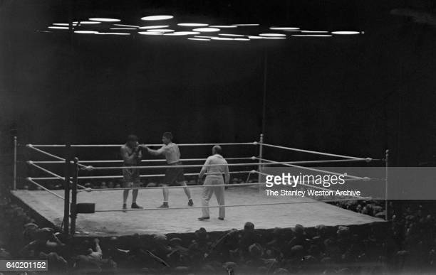 Gene Tunney throws a jab at Jack Dempsey as referee Tommy Reilly watches at Sesquicentennial Stadium Philadelphia Pennsylvania September 23 1926 Gene...