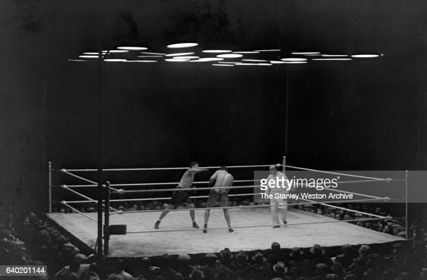 Gene Tunney throws a right to the head of Jack Dempsey as referee Tommy Reilly watches at Sesquicentennial Stadium Philadelphia Pennsylvania...