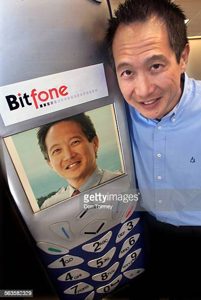Gene Wang Chairman and CEO of Bitfone Corp next to a lifesize cellphone electronic message board that displays his photo as well as displaying the...