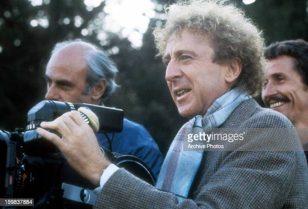 Gene Wilder operates the camera on set of the film 'The Woman In Red', 1984.