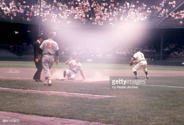 Gene Woodling of the Baltimore Orioles slides as third baseman Eddie Yost of the Detroit Tigers follows the play during an MLB game on June 28 1959...