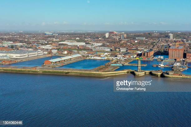 General aerial drone view of Liverpool Football Club and Everton's Goodison Park in the background with the Bramley Moore Dock in the foreground,...