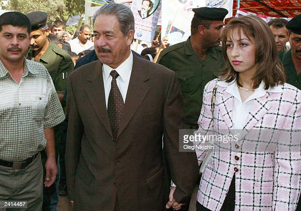 General Ali Hassan al Majeed known as 'Chemical Ali ' walks next to his wife during a referendum October 15 2002 in Baghdad Iraq Military officials...