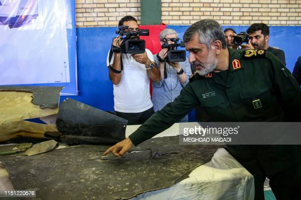 General Amir Ali Hajizadeh Iran's Head of the Revolutionary Guard's aerospace division speaks to media next to debris from a downed US drone...
