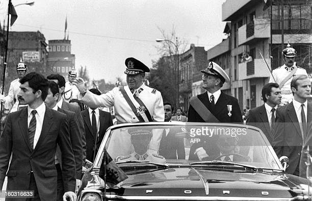 General Augusto Pinochet head of the Chilean military junta waves from the motorcade 11 September 1973 in Santiago shortly after his coup that killed...