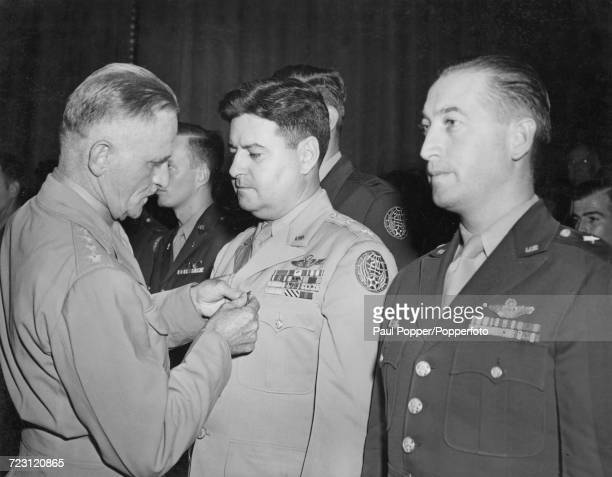 General Carl Andrew Spaatz Commander of Strategic Air Forces in the Pacific left pins the Distinguished Flying Cross on Major General Curtis LeMay as...