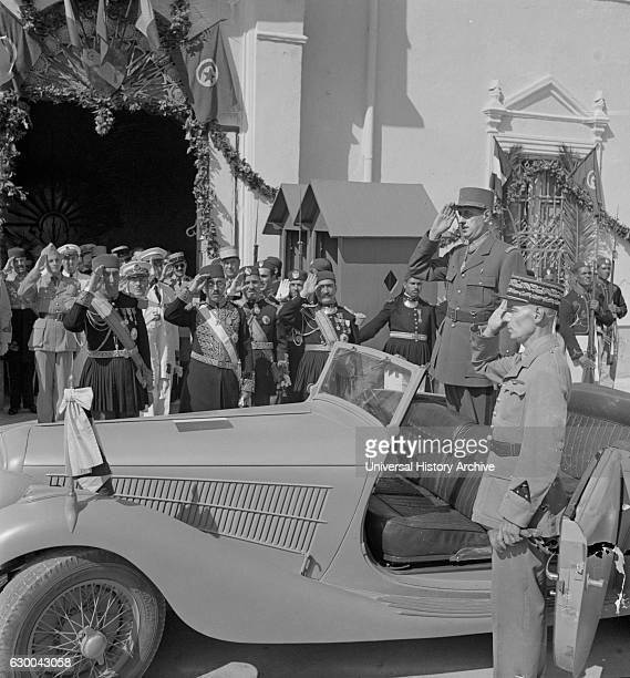General Charles de Gaulle Accompanied by General Charles Mast Saluting as Band Plays Marseillaise Outside Summer Palace of Bey of Tunis Carthage...