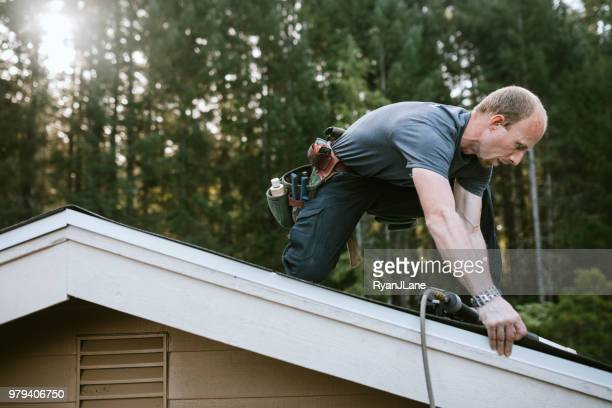 general contractor installing new roof - tree man syndrome stock photos and pictures