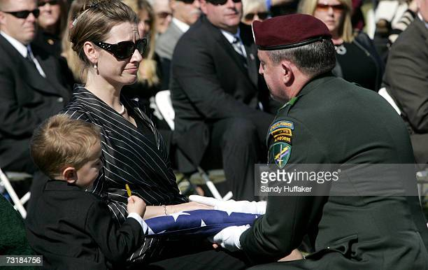 General David Morris hands Charlotte Freeman a flag from her husband's coffin during a memorial service at Ft Rosecrans National Cemetery on February...