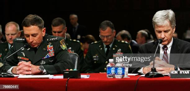 General David Petraeus and US Ambassador to Iraq Ryan Crocker observe a moment of silence for victims of the September 11th attacks before the start...
