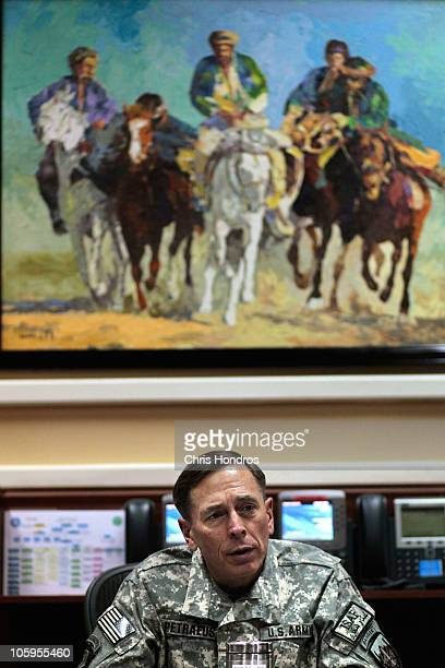 General David Petraeus commander of the International Security Assistance Force in Afghanistan talks at his desk under a painting of a traditional...