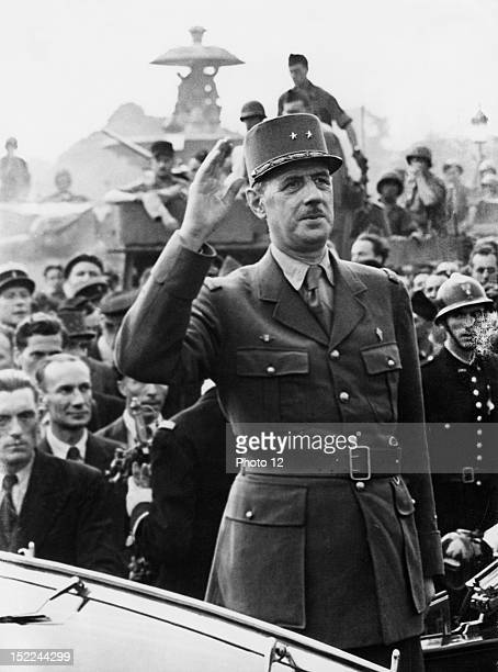 General de Gaulle president of the French Committee of National Liberation raises his hand in greeting to thousands of cheering Parisians August 25...
