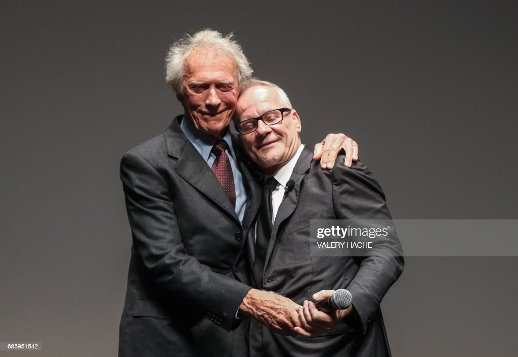 General Delegate of the Cannes Film Festival Thierry Fremaux (R) greets US director Clint Eastwood on stage on May 20, 2017, prior to the presentation of the 4K remaster of Eastwood's 1992 film 'Unforgiven' at the 70th edition of the Cannes Film Festival in Cannes, southern France. / AFP PHOTO / Valery HACHE