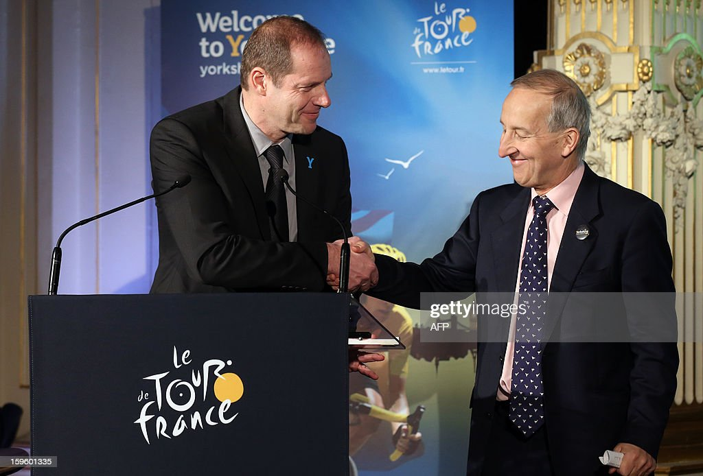 General director of the Tour de France Christian Prudhomme (L) shakes hands with Britain's ambassador to France, Peter Ricketts on January 17, 2013 in Paris, during the official presentation of the 2014 Tour de France's 'Grand depart' (Great departure). The 2014 Tour de France will start with a stage between Leeds and Harrogate in the northern English county of Yorkshire on July 5, organisers of cycling's most prestigious and gruelling race announced today.