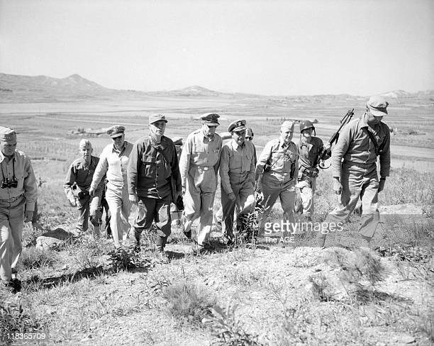 General Douglas MacArthur and staff walk up a hill to see over the front line during the Korean war 1950