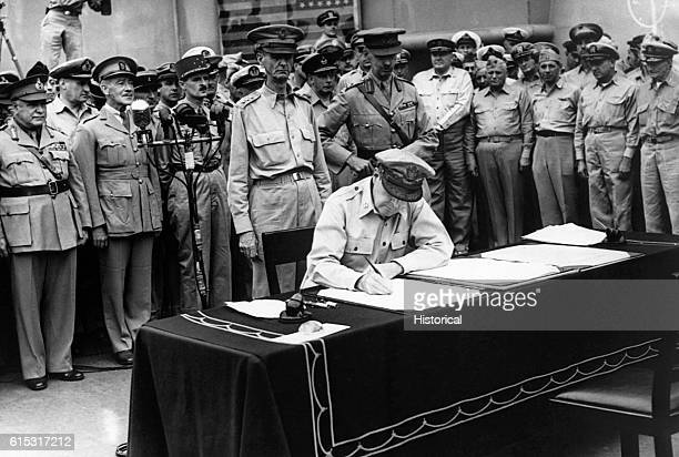 General Douglas MacArthur Supreme Commander of the Armies of the United States signs the instrument of Japanese surrender aboard the USS Missouri in...