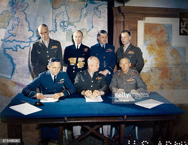 General Dwight D. Eisenhower is shown with his staff. Left to right, seated: Air Chief Marshall Sir Arthur Tedder, General Eisenhower and General Sir...