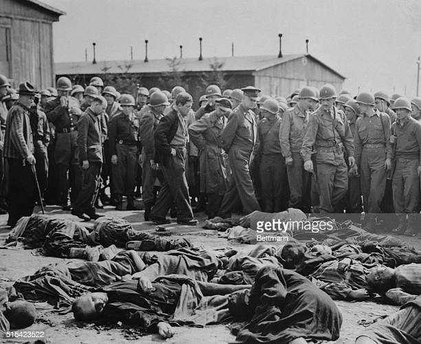General Dwight D Eisenhower on a tour of the Third Army Front here walks around a cluster of corpses representing the remains of many of the inmates...