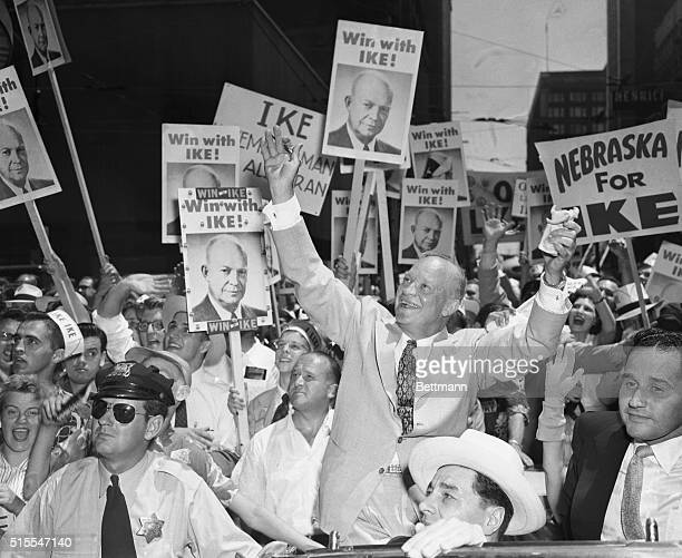 General Dwight D. Eisenhower raises his arms to acknowledge cheers from supporters during a motorcade from Chicago Nortwestern Station to the Hotel...