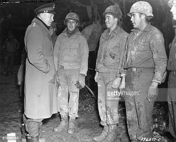 General Dwight D Eisenhower Supreme Allied Commander stops on a muddy road to talk to a group of GIs during his recent tour of the front lines