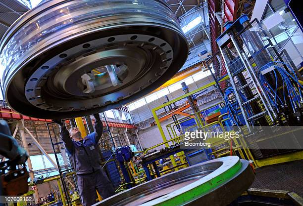 A General Electric Co employee positions a component for a gas turbine at the company's factory in Belfort France on Tuesday Dec 14 2010 General...