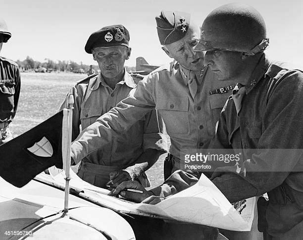 General George Patton of the United States in discussion with one of his staff whilst Field Marshal Bernard Montgomery looks on during a strategy...