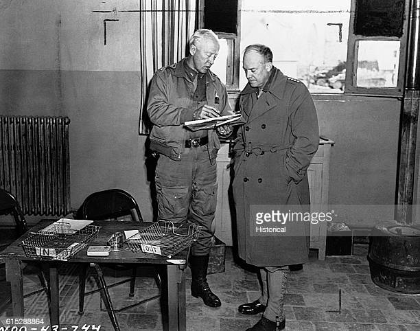 General George S Patton confers with General Dwight Eisenhower while looking at a map Eisenhower was Supreme Commander of Allied forces during the...