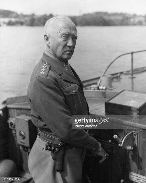 General George S. Patton, Jr., commanding general, US Third Army, smartly skippers a motor launch, captured by the 3rd Cavalry Group, on Lake...