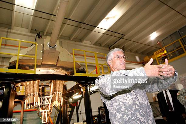 General George W. Casey, Jr., chief of staff for the U.S. Army, gestures while talking about a new Future Combat Systems cannon, seen at rear, at the...