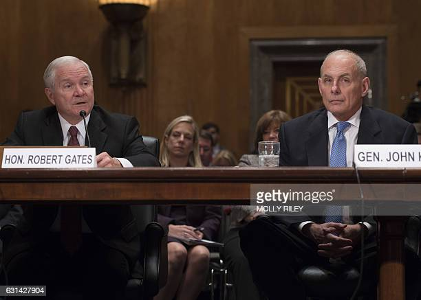 General John Kelly USMC listens while former Secretary of Defense Robert Gates gives a statement endorsing him at the Senate Homeland Security and...